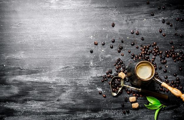 Kaffeekanne mit kaffeebohnen, rohrzucker und frischen blättern. auf einer schwarzen tafel.