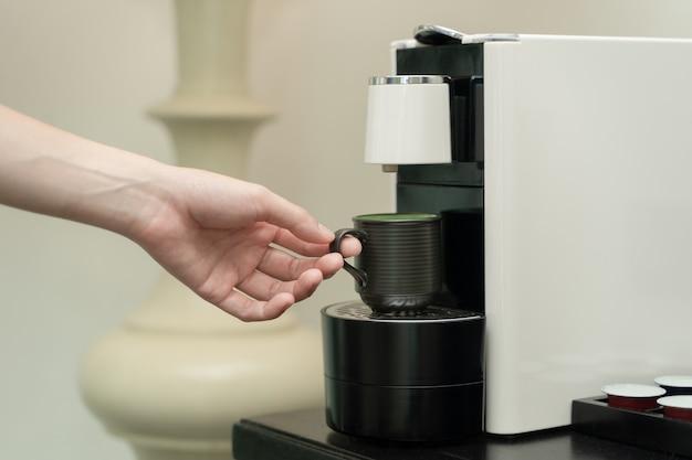 Kaffeekapselmaschinenhersteller. hand nimmt eine keramik tasse kaffee auf die kaffeemaschine.