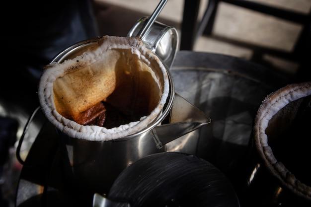 Kaffeekessel im thailändischen traditionellen korb der weinlese auf metall