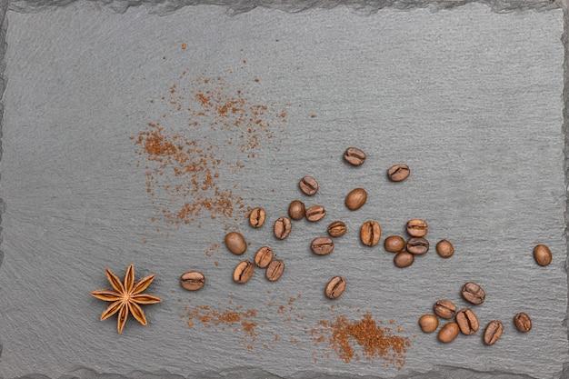Kaffeekörner, sternanis und gemahlene kaffeebohnen auf schwarz. flach legen