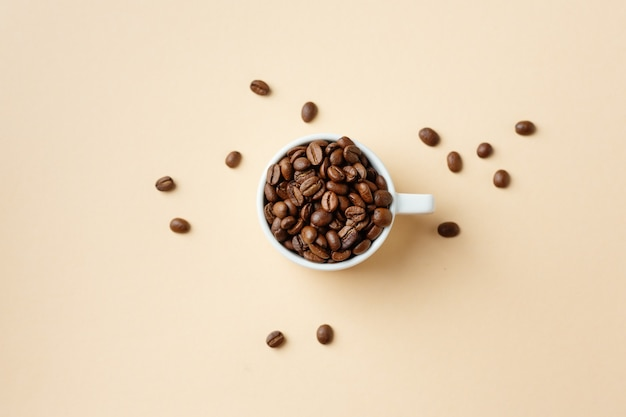 Kaffeekonzept mit kaffeebohnen in der tasse. draufsicht.