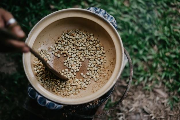 Kaffeekonzept: rösten von kaffeebohnen in einer in brand gesetzten keramikkanne mit einem holz zum rösten der kaffeebohnen.