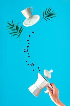 Kaffeemaschine des keramikofens in der hand der frau. trendige levitation. fliegende kaffeebohnen und espressotasse mit untertasse. blaue minzwand mit palmblättern, textraum.