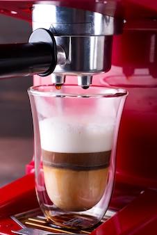 Kaffeemaschine, die cappuccino im doppelten glas zubereitet