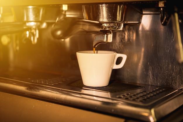 Kaffeemaschine, die einen koffeinfreien kaffee in eine weiße tasse setzt