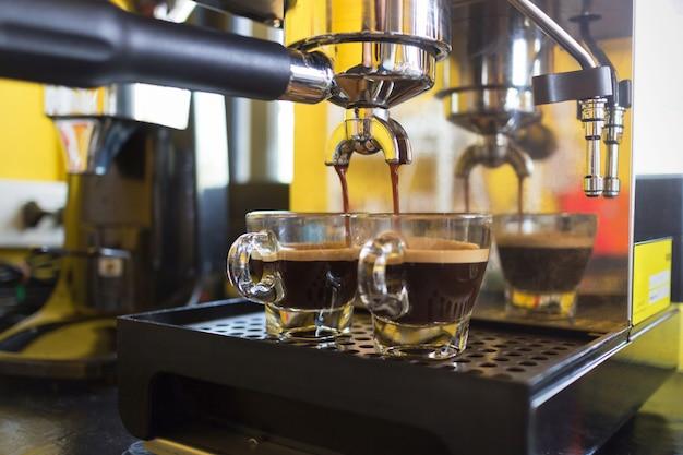 Kaffeemaschine, die frischen kaffee zubereitet und in schalen im café gießt.