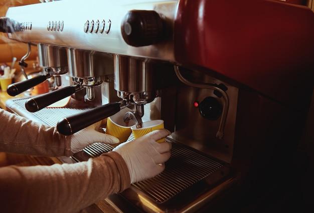 Kaffeemaschine gießt kaffee auf gelbe pappkaffeetasse in der bar. beschnittenes bild. nahansicht