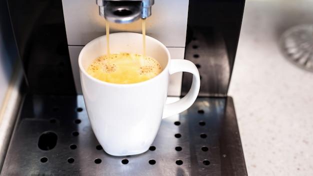 Kaffeemaschine gießt kaffee mit in eine tasse