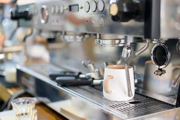 Kaffeemaschine macht schwarzen kaffee und gießt in eine tasse im café
