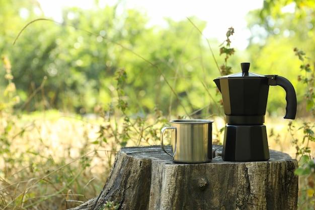 Kaffeemaschine und metallbecher auf baumstumpf im freien