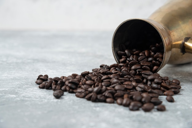 Kaffeemaschine voller gerösteter kaffeebohnen auf marmoroberfläche.