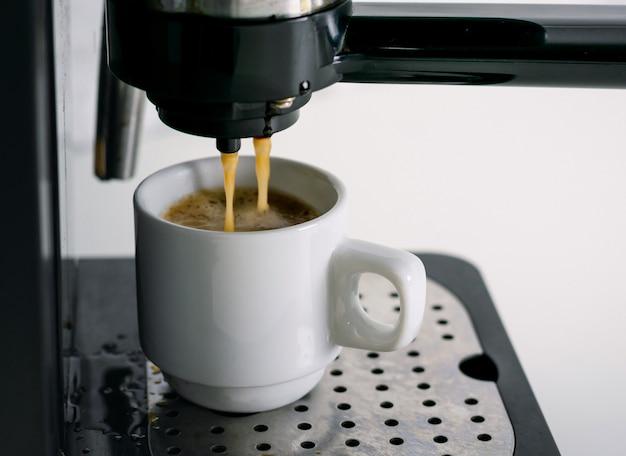 Kaffeemaschinenextraktion in eine kaffeetasse