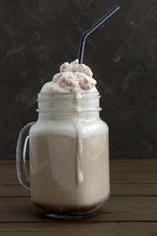 Kaffeemilchshake mit auf hölzernem hintergrund.