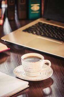 Kaffeemorgen am arbeitsplatz. mit einem buch oder laptop. selektiver fokus.