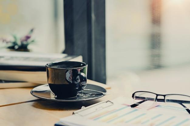Kaffeemorgenweinlesetonfoto, kaffeetasse auf geschäftsschreibtisch.