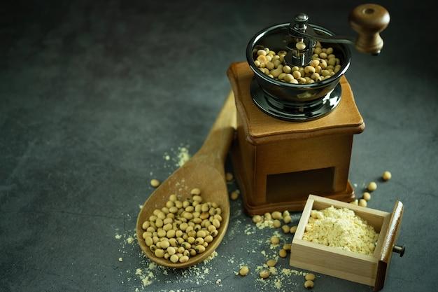 Kaffeemühle, die sojabohnen in der dunkelheit zu pulver und holzpfanne mahlt.