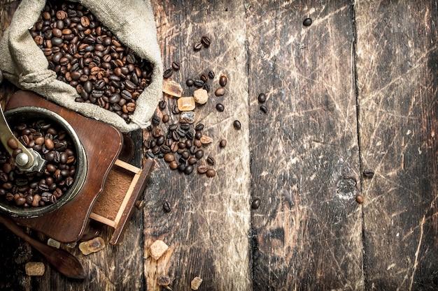 Kaffeemühle mit kaffeebohnen. auf einem hölzernen hintergrund.