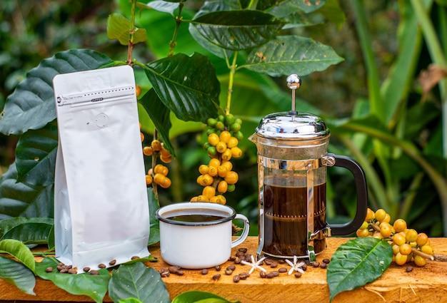 Kaffeepackungen und kaffeemaschinen in komposition mit der landschaft, dem tisch und dem wald