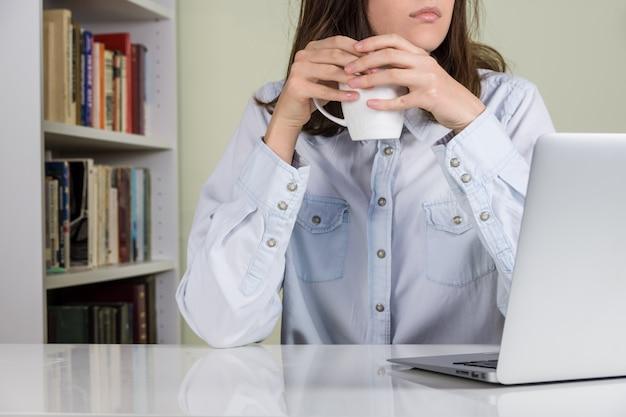 Kaffeepause am weißen schreibtisch im heimbüro