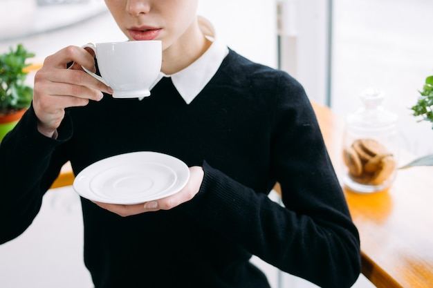 Kaffeepause. büroangestellte oder geschäftsfrau im café, die heißes getränk aus einer weißen tasse trinkt