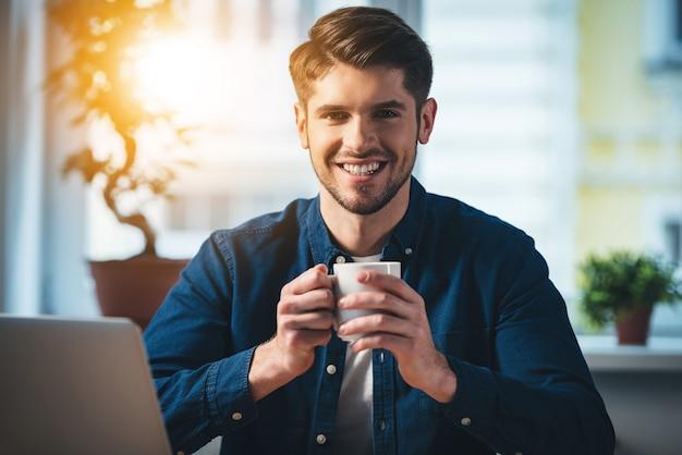 Kaffeepause. fröhlicher junger gutaussehender mann, der eine kaffeetasse hält und mit einem lächeln in die kamera schaut