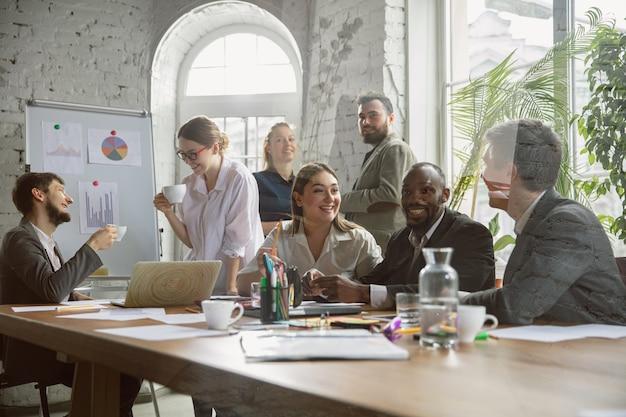Kaffeepause. gruppe junger geschäftsleute, die ein treffen haben. diverse gruppe von mitarbeitern diskutieren neue entscheidungen, pläne, ergebnisse, strategie. kreativität, arbeitsplatz, geschäft, finanzen, teamwork.