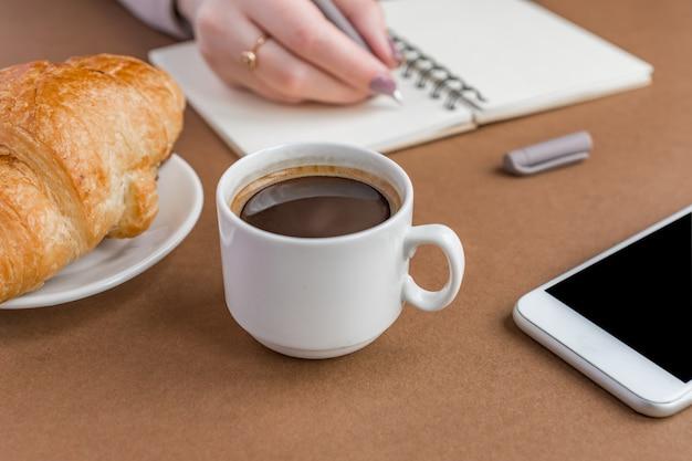 Kaffeepause mit croissant und espressomaschine. frauenschreiben auf notizbuch. freiberufler bei der arbeit