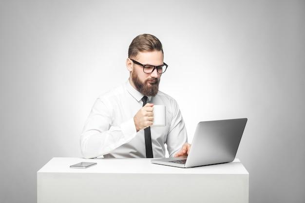 Kaffeepause! porträt eines gutaussehenden, glücklichen, bärtigen jungen geschäftsmannes in weißem hemd und schwarzer krawatte sitzen im büro und machen eine pause mit einer tasse kaffee und einem lächeln schauen auf den laptop. isoliert
