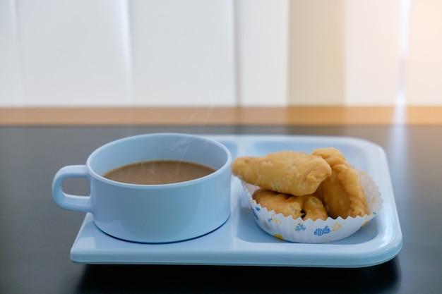 Kaffeepause stellte eine heiße getränkschale und -snack im papierplatz auf schwarzer tabelle für die entspannung ein
