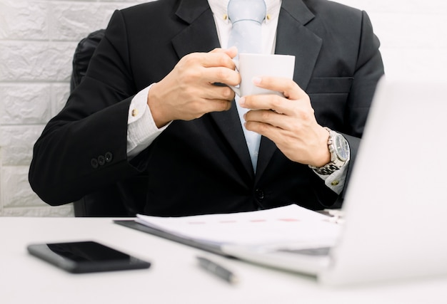Kaffeepausengeschäftsmann, der arbeitet, entspannen sich auf laptop an seinem schreibtisch.