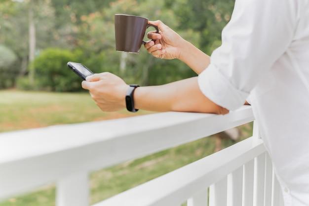 Kaffeepausengeschäftsmann, der kaffee hält und smartphone auf balkon betrachtet.