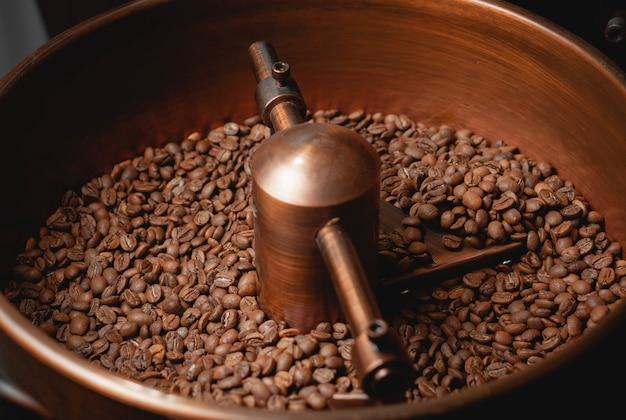 Kaffeeproduktion. geröstete spinnkühler-profimaschinen und frische braune kaffeebohnen
