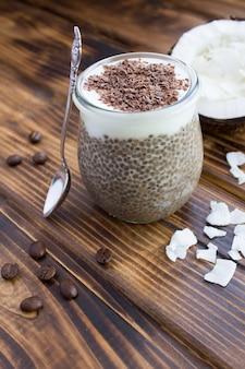 Kaffeepudding mit chia, kokosmilch und schokolade im glas auf der braunen holzoberfläche. lage vertikal.