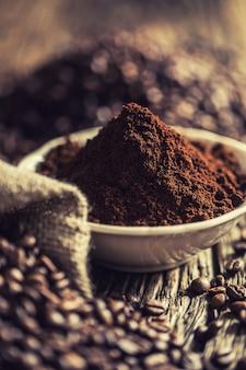 Kaffeepulver in weißer schüssel mit bohnen.