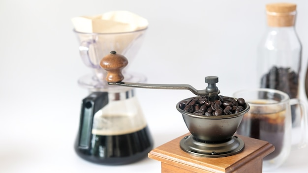 Kaffeesatz, frisch geröstete kaffeebohnen in der manuellen kaffeemühle der mühle und schwarzer kaffeepapiertropfen der glasflasche isoliert