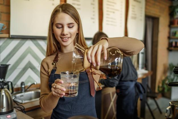 Kaffeeset, übergießen und kaffeekessel. barista frau, die alternative brauverfahren tut
