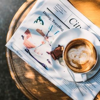 Kaffeestube-café latte cappuccino-zeitungs-schokoladenkuchen-konzept