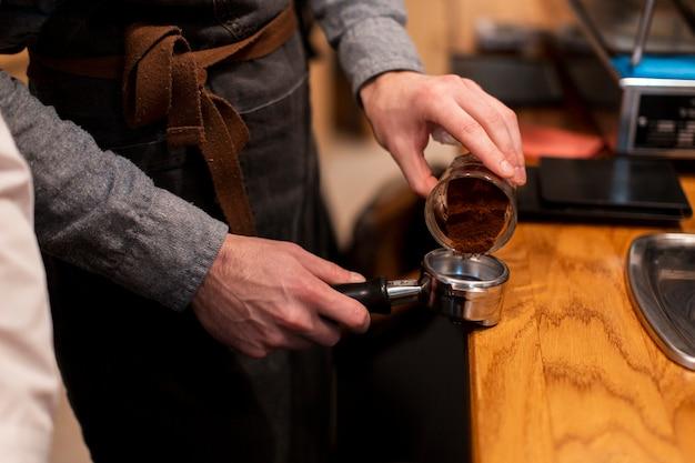 Kaffeestubemitarbeiter, der kaffee macht