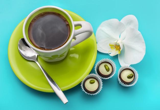 Kaffeesüßigkeiten und weiße orchidee auf blau