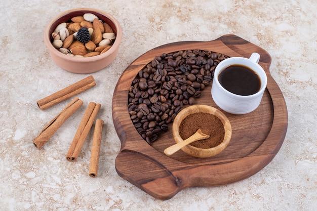 Kaffeetablett neben zimtstangen und einer kleinen schüssel mit verschiedenen nüssen