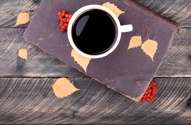 Kaffeetasse, altes buch, herbstlaub und getrocknete eberesche auf hölzernem hintergrund