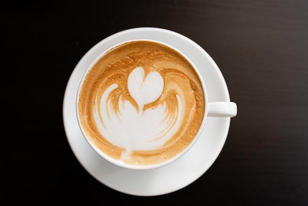 Kaffeetasse auf braunem holzuntergrund (kaffee, oben)