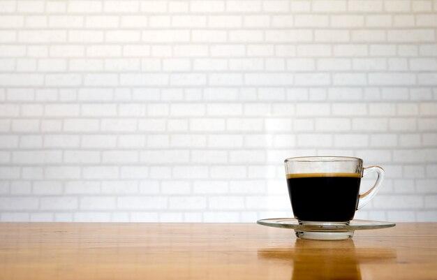 Kaffeetasse auf bretterboden mit weißem backsteinmauerhintergrund.