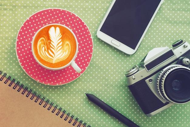 Kaffeetasse auf dem schaum mit zeichnung und einer fotokamera