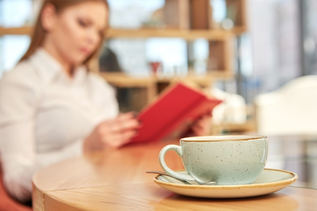 Kaffeetasse auf dem vordergrund, frau, die ein buch liest