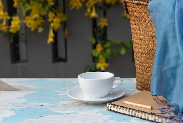 Kaffeetasse auf hölzerner tabelle mit braunem notizbuch