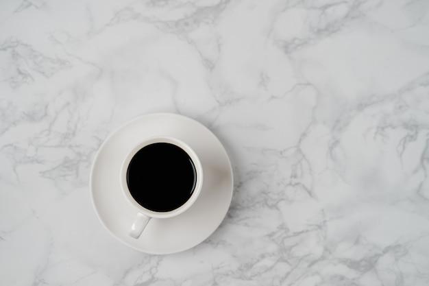 Kaffeetasse auf marmorbeschaffenheitstabelle, schwarze kaffeetasse in der draufsicht mit copyspace