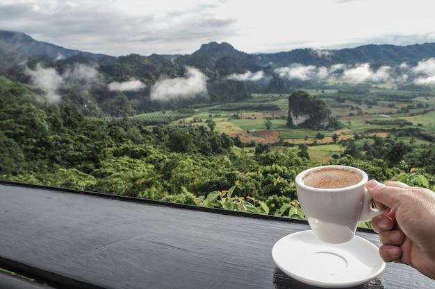 Kaffeetasse auf tabelle mit bergblicken morgens als hintergrund