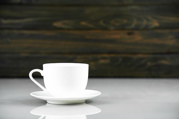 Kaffeetasse auf tabelle mit hölzernem hintergrund
