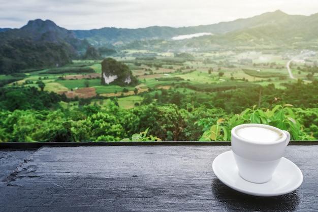 Kaffeetasse auf tisch mit bergblick morgens